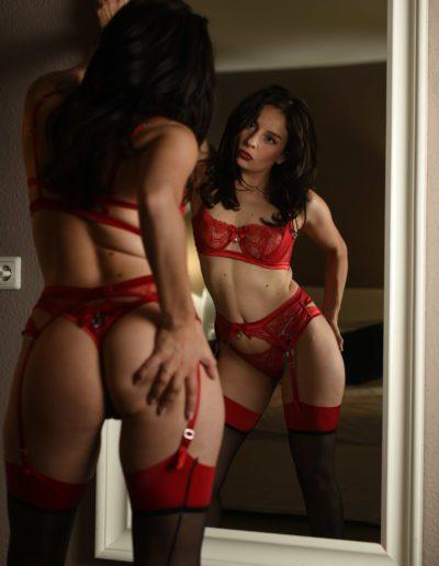 Mia Elysia Escort rote Wäsche vor dem Spiegel